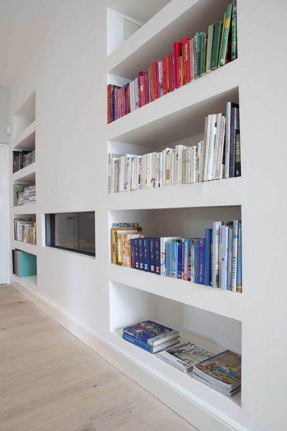 Een opgeruimde, minimalistische boekenkast op kleur gesorteerd Marie Kondo